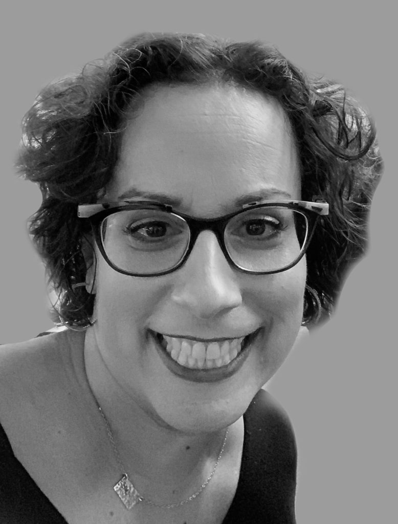 White woman with short curly hair and dark rimmed glasses smiles at camera